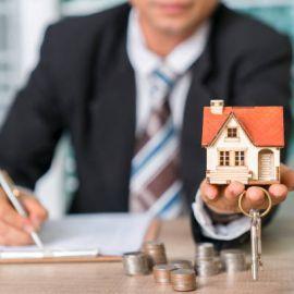 Homme en costard qui tient la maquette d'une maison et des clefs dans sa main, avc quelques pièces de monnaie posées sur le bureau