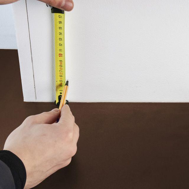 personne qui mesure une planche en bois